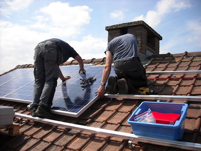 two men installing solar panels in the roof