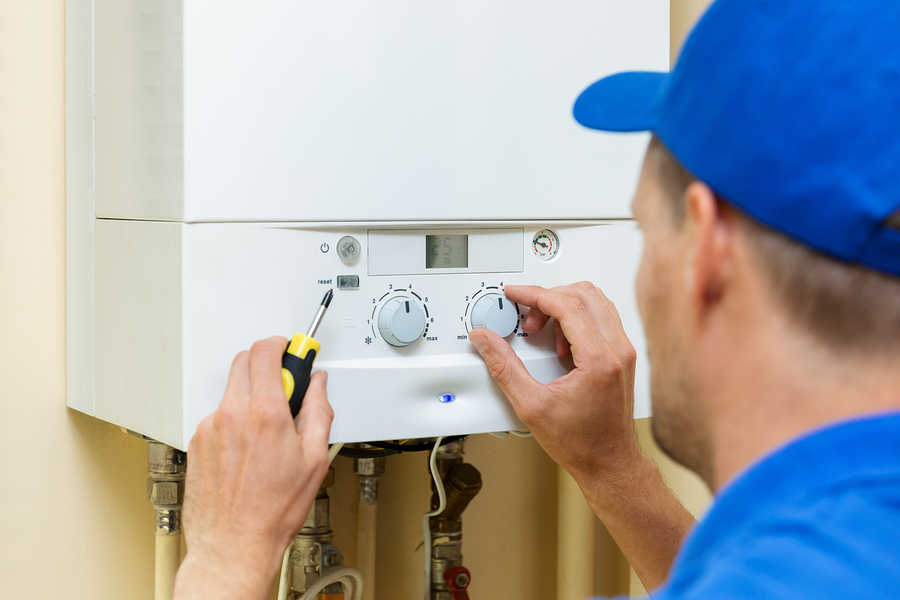 Plumber in Wellington setting up a central gas heating boiler at home
