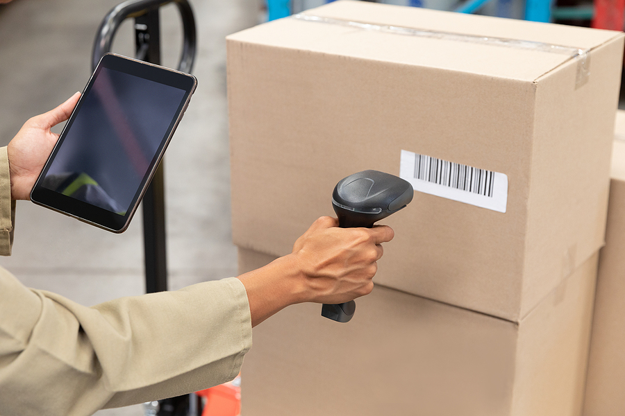 Female worker scanning packages for reverse logistics