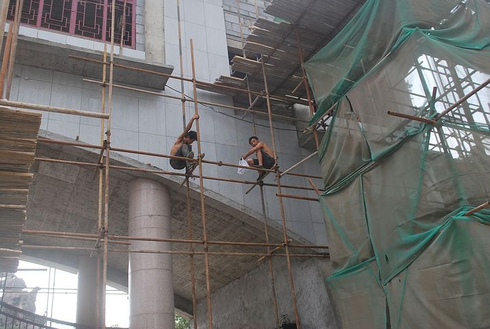 Construction workers standing in scaffold